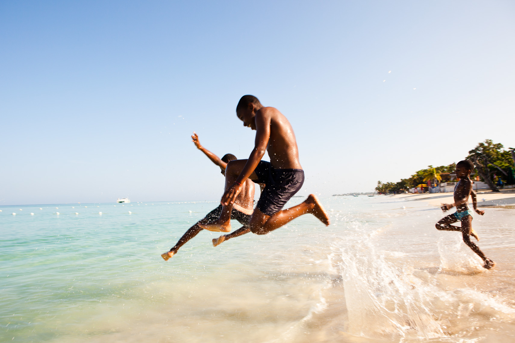 Jamaican kids jumping in ocean.